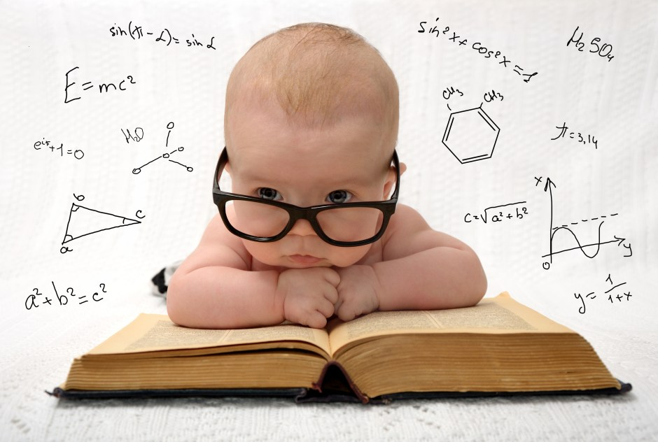 funny portrait of cute baby in glasses lieing on old book and thinking of all the knowledge in the world