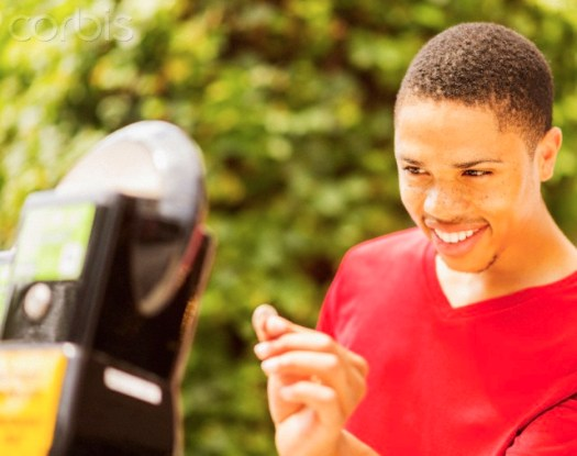 19 Jun 2014 --- African American man paying parking meter --- Image by © JGI/Daniel Grill/Blend Images/Corbis