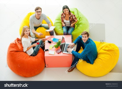 stock-photo-creative-work-space-top-view-of-four-cheerful-young-people-working-together-and-looking-up-while-299889053-1