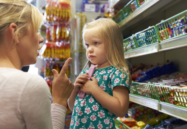 Girl Having Arguement With Mother At Candy Counter In Supermarket