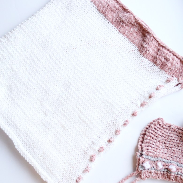 This free knitting pattern is for a newborn wrap that is knitted flat with bobbles along one side and a velvety texture along the top.