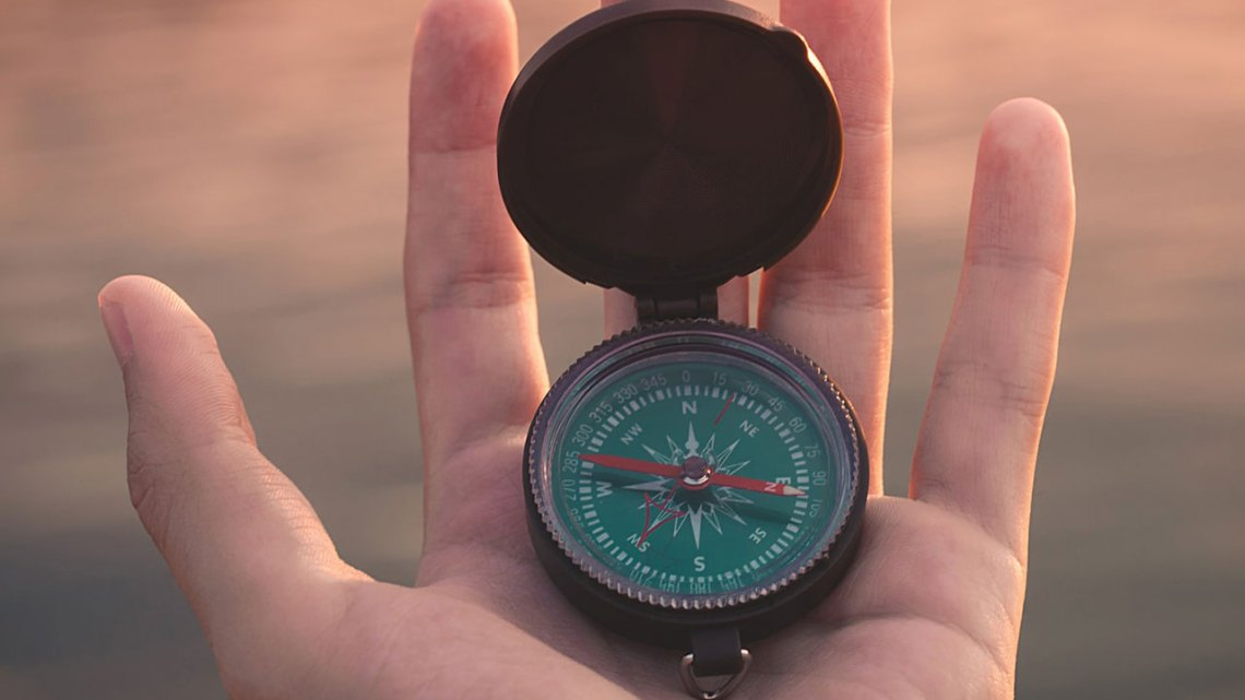 A hand holding a compass demonstrates the marketing path forward in COVID-19 pandemic.