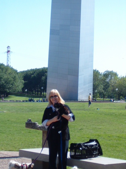 Sherra holds Oreo in front of the arch.