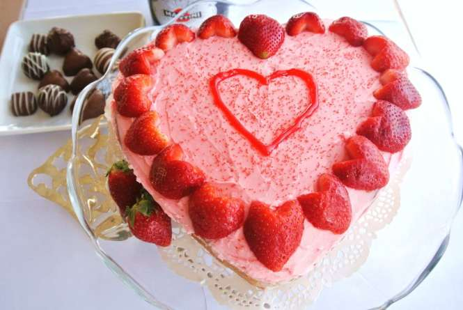 Heart-shaped naked cake with heart-shaped fresh strawberries