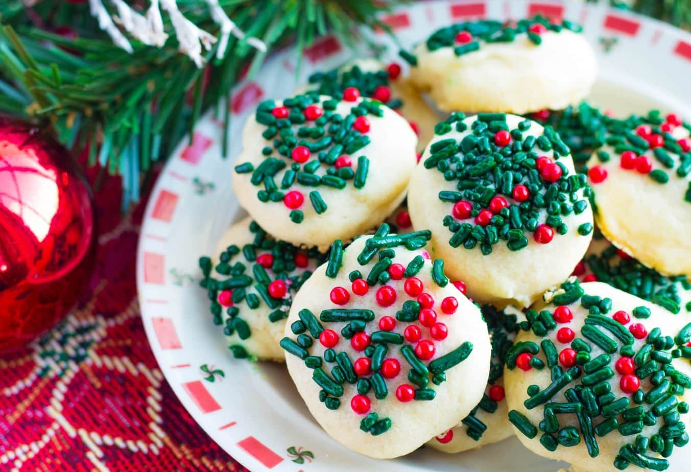 Easy Christmas Butter Cookies with Sprinkles will melt in your mouth with butter flavor! These festive cookies are easy to prep and decorate with your kids!