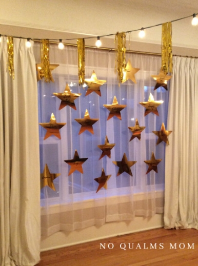 Foil stars were personalized with guest names and hung with fishing line over inexpensive sheers.