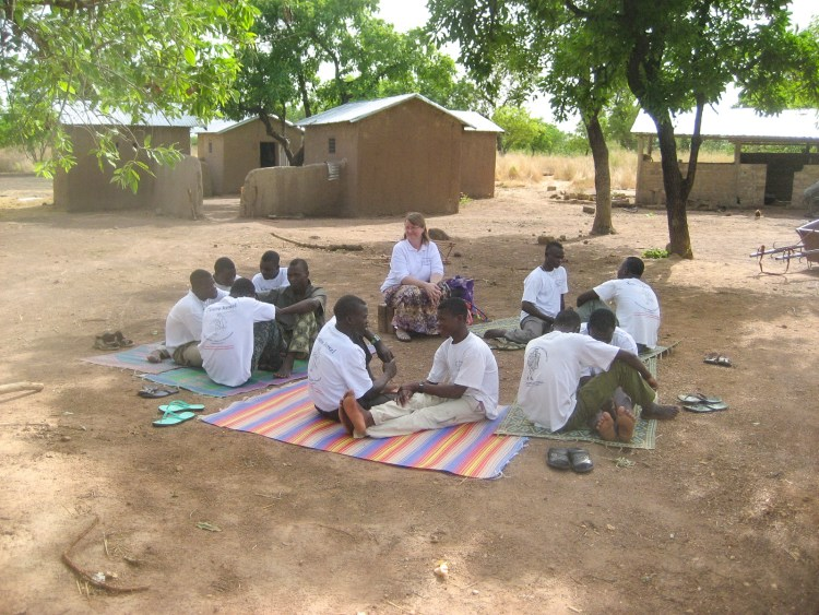 Beninese pastors sitting in a circle on colorful mats on the ground in front of some mud brick buildings practicing telling a story in pairs while Nora watches, beaming.