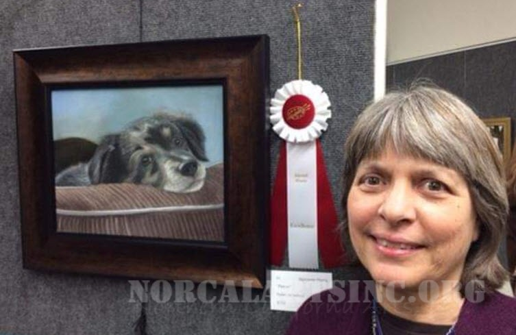 Artist Marianne Harris standing by her pastel portrait of an australian shepherd dog