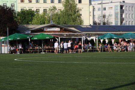 Blick über das Spielfeld zur Kantine mit vielen Menschen davor und darin