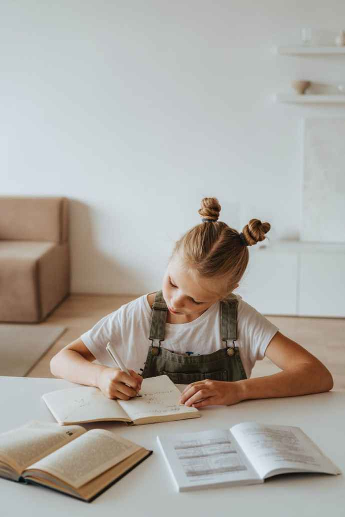 little girl writing on a notebook