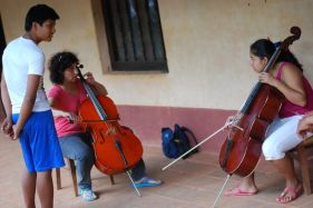 An Argentinian string teacher visiting Santa Ana working with bow hold and other basic skills for strings.