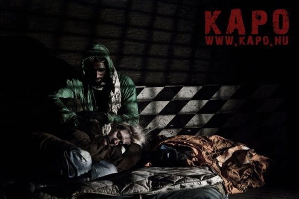 Person cowering in a prison with the Kapo logo