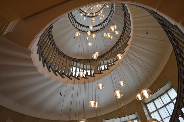 a spiral staircase with lights hanging down