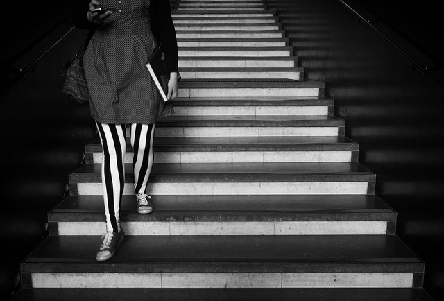 a woman in striped tights descends a staircase