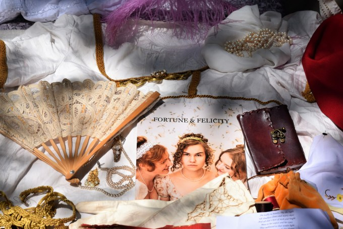 a fan, book, and Fortune & Felicity poster