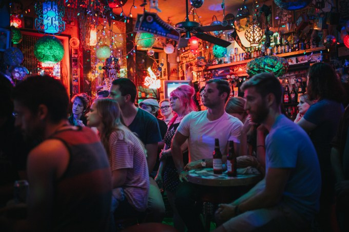 Several people sit in the audience of a club listening