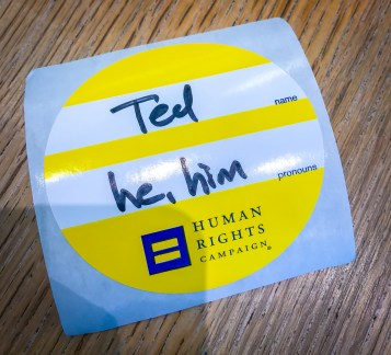A pronoun sticker with Ted's pronouns listed as he, him