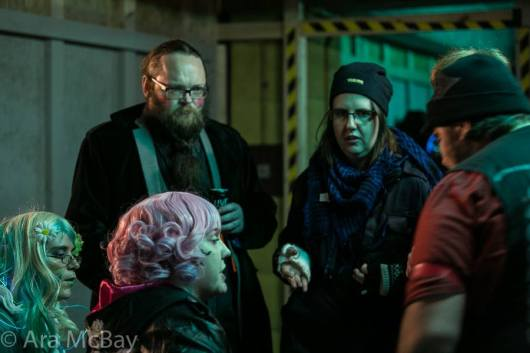 a group of characters confer in a dystopian setting