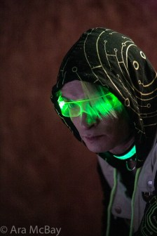 man in hoodie, glowing glasses, and green collar