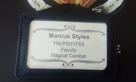 A New World Magischola badge listing pronouns