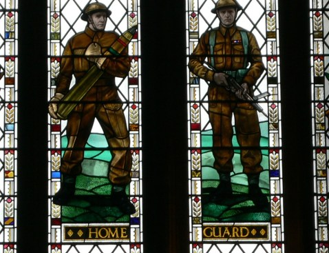 Two stained glass soldiers with the words Home Guard underneath