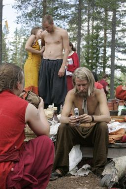 People in costuming with a blonde bearded person checking a cell phone