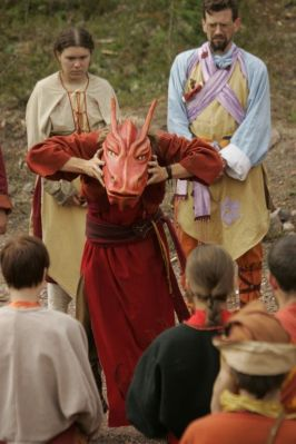 Person in long red costume and a dragon mask encircled by other costumed people