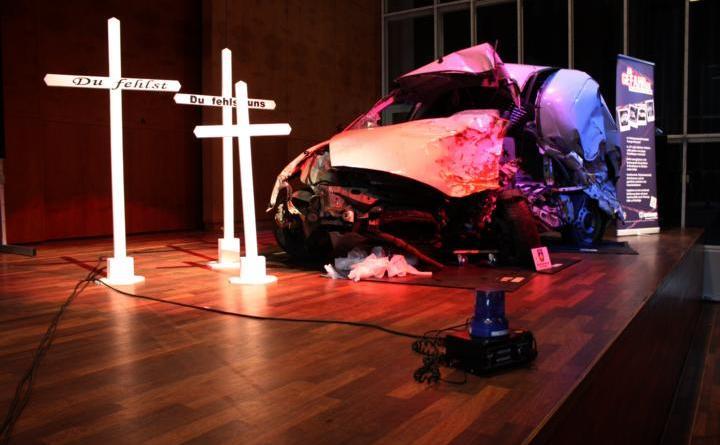 Ein Autowrack steht auf der Bühne, daneben drei Kreuze. Am Dienstagvormittag haben rund 700 Schülerinnen und Schüler den Schilderungen der Rettungskräfte von tödlichen Unfällen zugehört. Foto: Stadt Papenburg