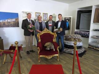 """Ortsbürgermeister Manfred Schonhoff (links) und Jonas Berger von der Wirtschaftsförderung der Stadt Lingen (rechts) begrüßten die Geschäftsführer des neuen Hundesalons """"Emshund"""", Romina Block und Patrice Krappmann, sowie die Hündin """"Mrs. Grey"""" in Laxten. Foto: Stadt Lingen"""