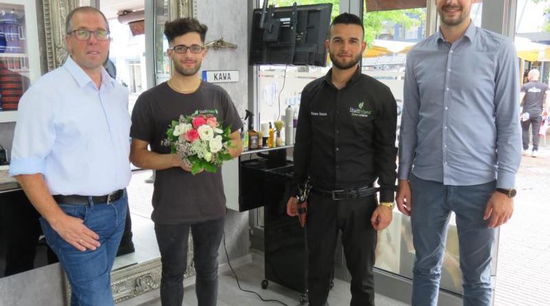 Andreas Löpker (links) und Jan Koormann (rechts) gratulieren Baziyan Koro (2.v.l.) und seinem Mitarbeiter Kawa Nasso zur Neueröffnung des StadtFriseurs. Foto: Stadt Lingen