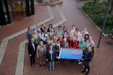 Zeigen Flagge als Zeichen gegen Gewalt an Frauen: Bürgermeister Markus Honnigfort (2.Reihe links), Gleichstellungsbeauftragte Christin Jönen (vorne rechts) sowie Vertreterinnen der Frauenverbände. Foto: Stadt Haren (Ems)