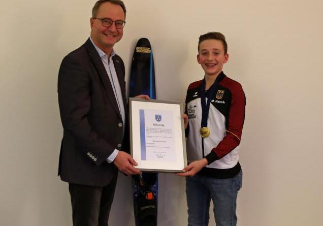Bürgermeister Markus Honnigfort überreicht dem Europameister im Wasserski Marvin Hasch eine Urkunde. Foto: Stadt Haren (Ems)
