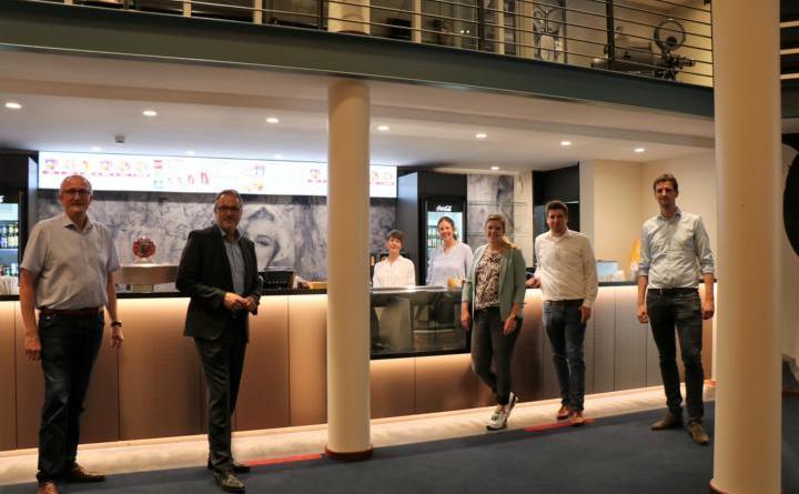 """Bei einer Führung mit der Familie Muckli durch das renovierte Kino konnten sich Bürgermeister Helmut Knurbein (2.v.l.), Erster Stadtrat Bernd Ostermann (links), Citymanagerin Janine Wester (3.v.r.), Wirtschaftsförderer Alexander Kassner (2.v.r.) und Stadtbaurat Enno Westrup (rechts) die neu gestalteten Kinosäle in Augenschein nehmen und sich dabei über eine Kostprobe des Surround-Sound-Format """"Dolby Atmos"""" freuen. Foto: Stadt Meppen"""
