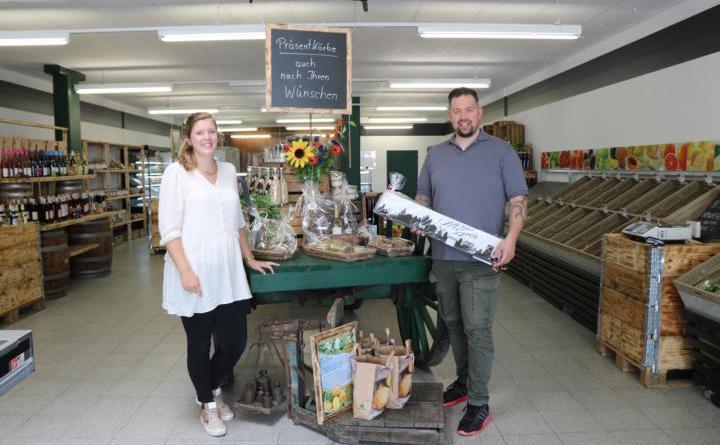 """Citymanagerin Janine Wester (links) gratuliert Geschäftsinhaber Ingo Kollmer (rechts) zur Neueröffnung des Bauernmarktes und überreicht als Geschenk die """"Meppener Skyline"""". Foto: Stadt Meppen"""