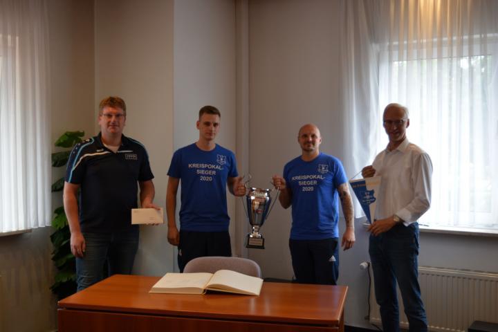 Mannschaftskapitän Maximilian David und der erfahrenste Mannschaftsspieler Alexander Roth zeigen stolz den Pokal, der für eine Saison zum SV Groß Hesepe gehört. Foto: Gemeinde Geeste