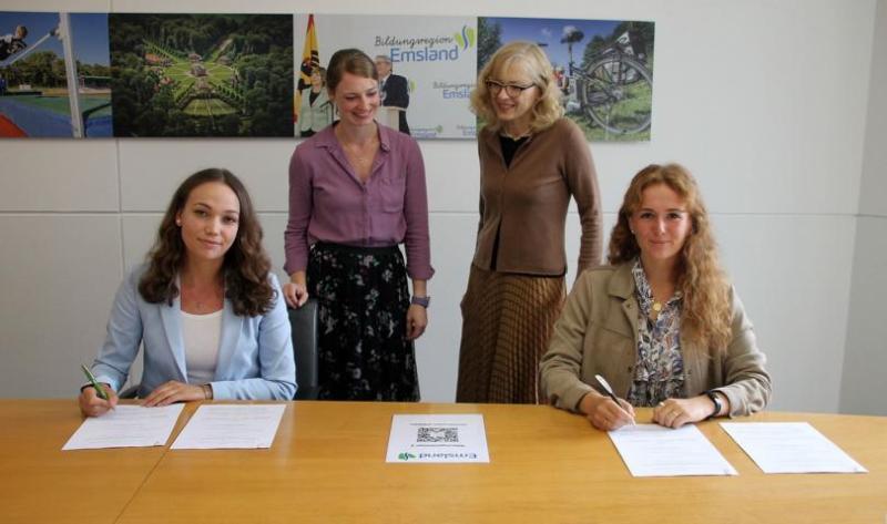Mara Stedem und Diana Tholen (vorne, v. l.) unterzeichnen die Stipendiatsvereinbarung mit dem Landkreis Emsland. Sozialdezernentin Dr. Sigrid Kraujuttis (stehend, r.) und Julia Thole von Meilenstein nahmen die neuen Stipendiatinnen in Empfang. (Foto: Landkreis Emsland)