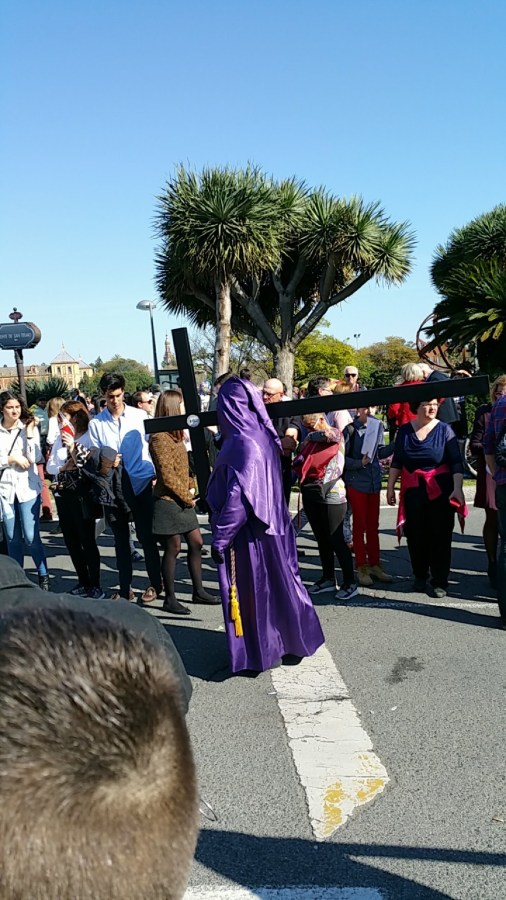 A+member+of+the+procession+in+a+traditional+capirote+carries+a+crucifix+as+part+of+the+celebration%0A