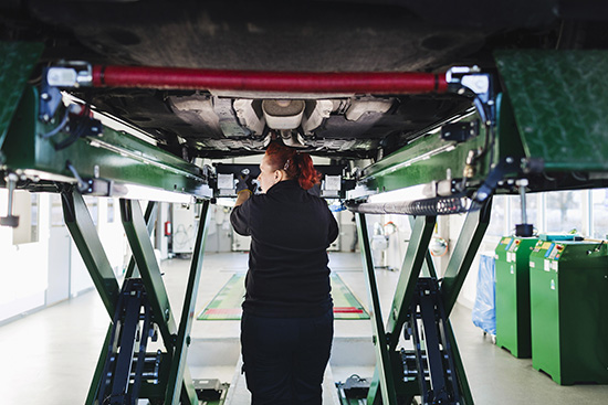 Rear view of female mechanic standing under car on hydraulic lift