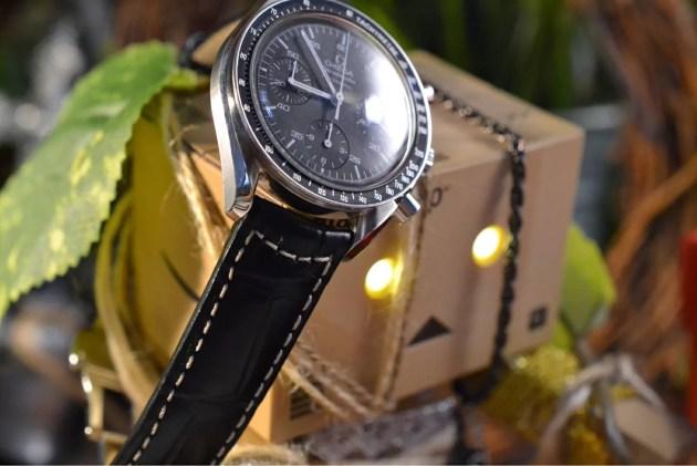 時計は白文字盤で黒革ベルト