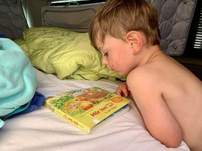 Junge sieht sich Buch im Bulli an