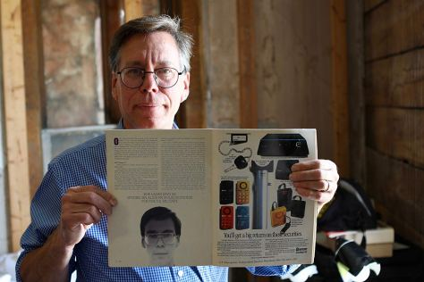 Bob Lazar holds up a magazine with his story in it.