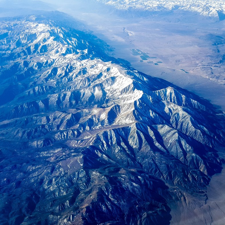 Large, impressive snow capped mountain ridge rising from valley on each side near Montgomery Pass, Nevada (looking south from airplane window)