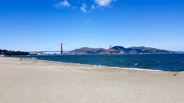 Long Distance view of the Golden Gate Bridge from the beach. Choppy water in the foreground on a super windy day.