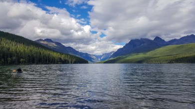 A solo boater rows on Bowman Lake in Glacier National Park