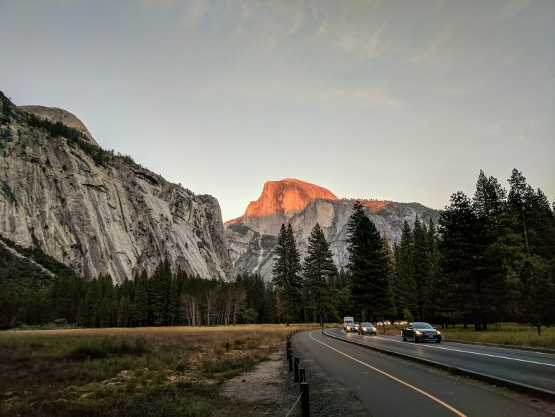 A line of cars drives towards Yosemite Valley exits while Half Dome is illuminated at sunset