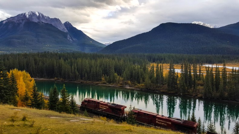 A red train engine travels along the Bow River with magnificent mountains in the background in Banff National Park, Canada