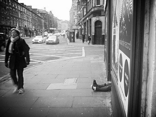 Photo of woman passing half-hidden homeless man in Edinburgh street.
