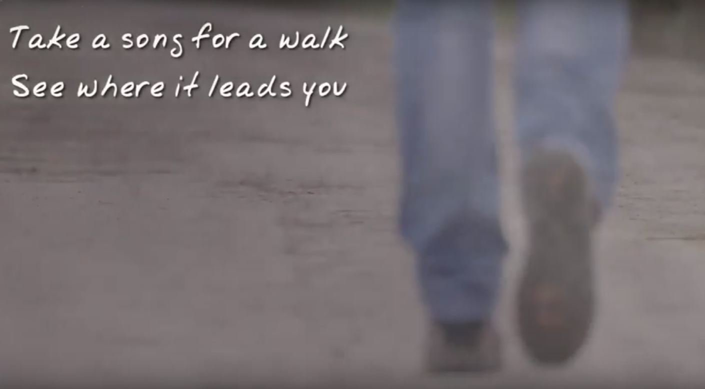 Image from video: two feet walking and words 'Take a song for a walk see where it leads you'