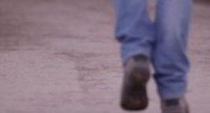 Photo of man's feet walking on misty road.