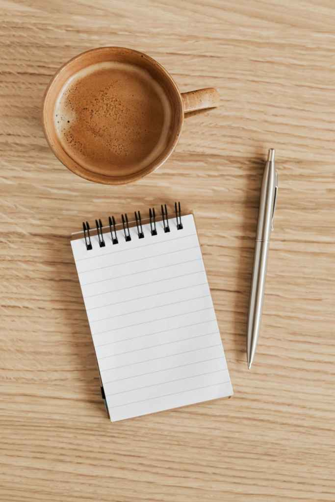 cup of espresso and notebook with pen